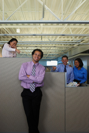 Colleagues laughing and pointing behind someoenes back Stock Photo