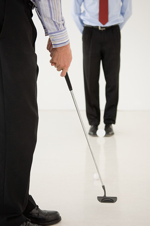 Two businessmen practicing golf
