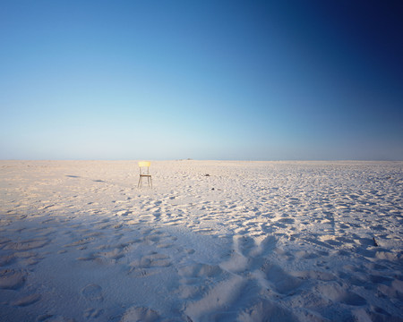A lonely chair on golden sand 版權商用圖片