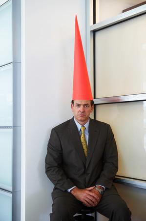 Businessman wearing dunce cap