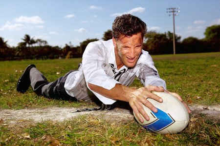 Businessman playing rugby