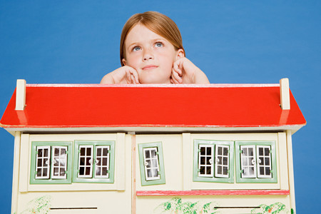 Girl leaning on doll house