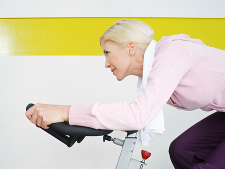 Woman on exercise bike in health club