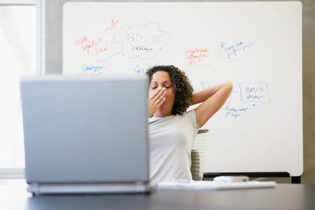 Woman yawning at computer Stock Photo