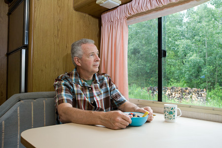 Man having breakfast in a caravan Banco de Imagens