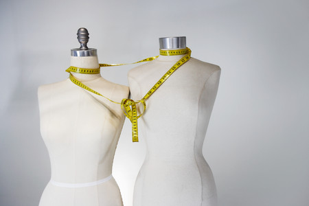 Tape measure tied around tailors dummies 写真素材