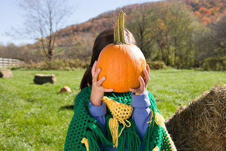 Girl holding pumpkin in front of her face