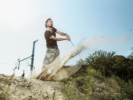Young man playing golf on wasteland Stockfoto