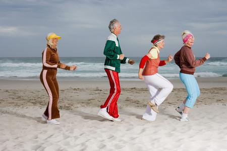 Cuatro adultos mayores corriendo en la playa