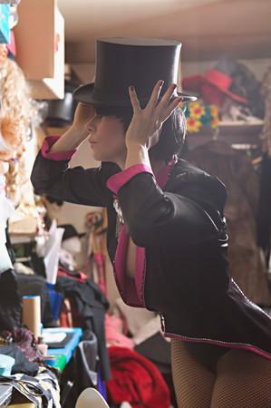 Performer adjusting her top hat