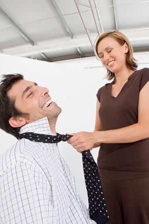Woman fastening mans tie
