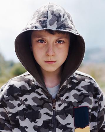 Boy in a hooded sweater Фото со стока - 116902024