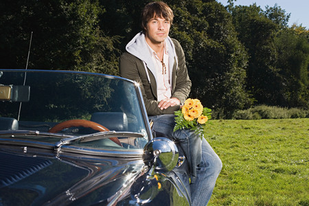 Man with a convertible and bunch of flowers