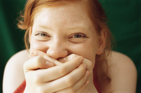 Girl laughing with hands over mouth Stock Photo