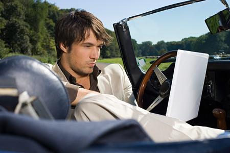 Man in convertible using laptop