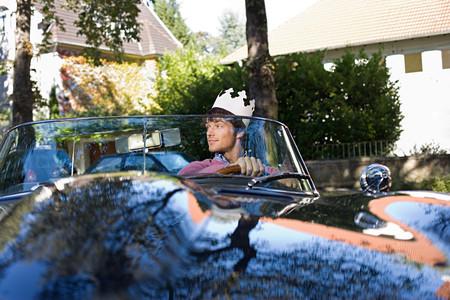 Man in car wearing paper crown Standard-Bild