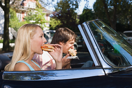 Couple eating burgers in convertible