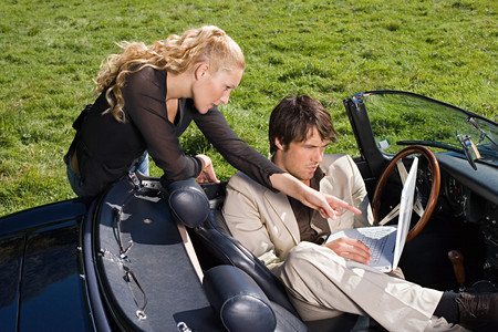 Couple in convertible with laptop Banco de Imagens
