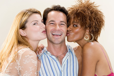 Man being kissed by two women