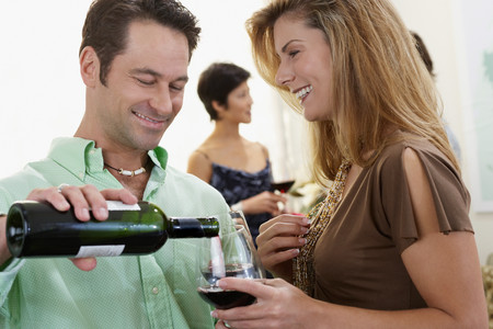 Host pouring wine for woman