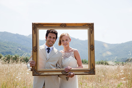 Newlyweds holding vintage picture frame Imagens