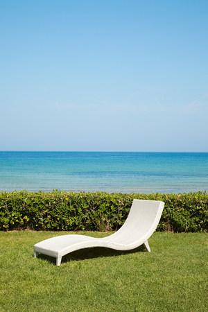 Empty white sun lounger on grass