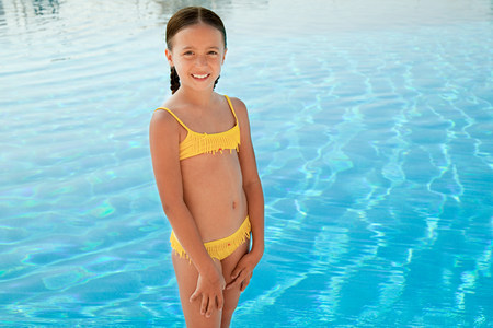 Girl in yellow bikini by swimming pool, portrait Banque d'images