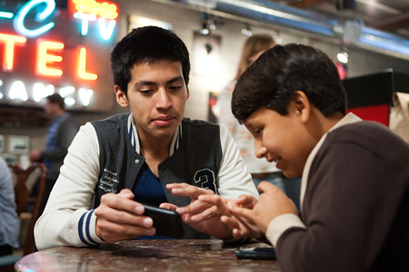 Two brothers with smartphone in cafe