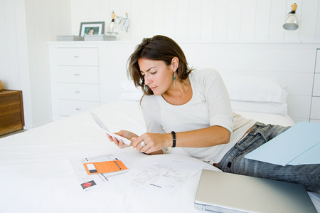 Woman on bed organising home finances Stock Photo