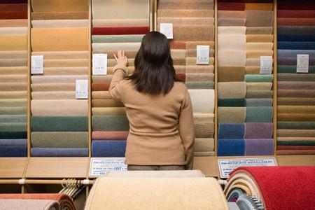 Woman choosing carpet Imagens