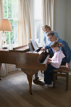 Parents with daughter playing piano 写真素材 - 115865888