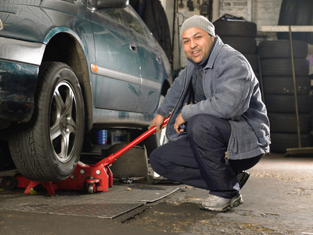 Mechanic using trolley jack Stock Photo