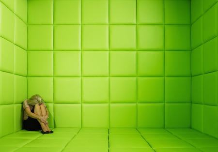Woman crouching in corner