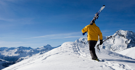 Male skier walking over mountain ridge
