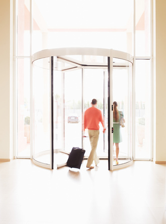Couple leaving hotel with luggage
