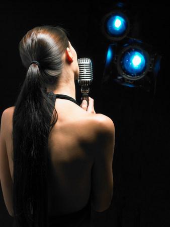 Parte posterior de la mujer cantando en el micrófono.