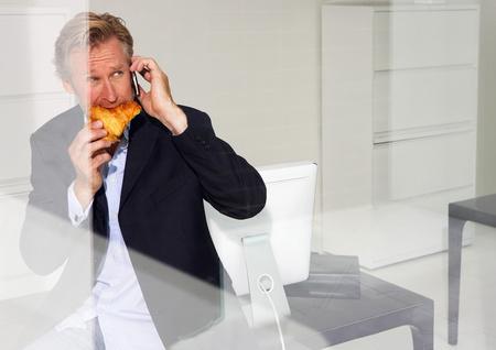 Man in office eating croissant Stock fotó