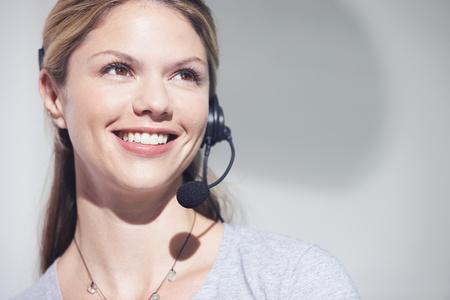 Mujer con auriculares de teléfono sonriendo. Foto de archivo