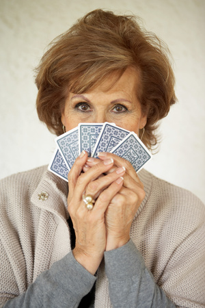 Senior woman holding playing cards 版權商用圖片