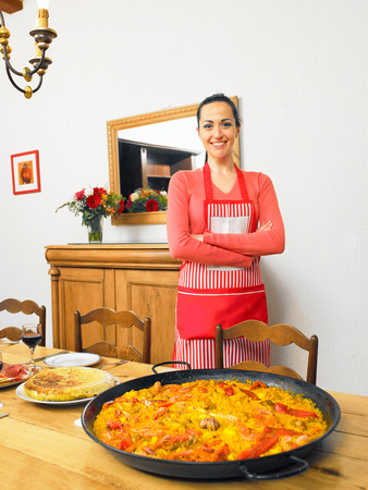 Young woman by large dish of paella