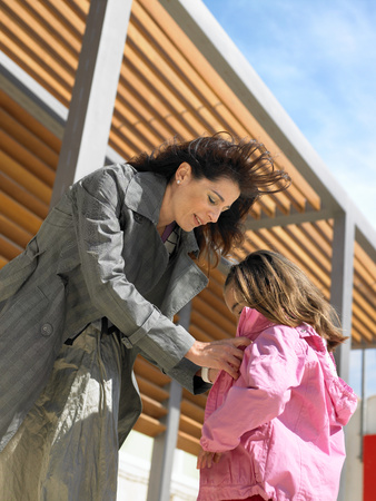 Mother helping daughter put on coat