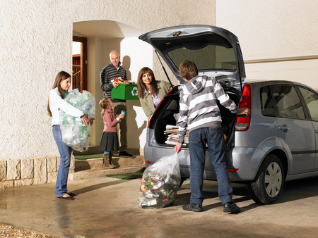 Family loading car boot with recycling