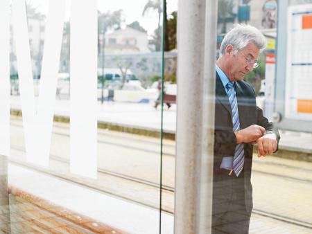 Senior businessman checking watch