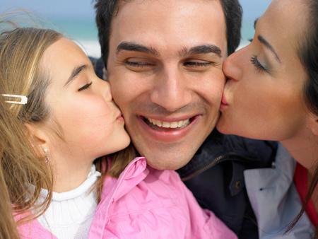Mutter und Tochter küssen Vater