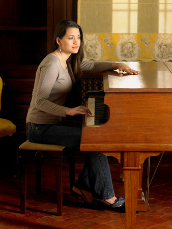 Young woman playing piano with one hand