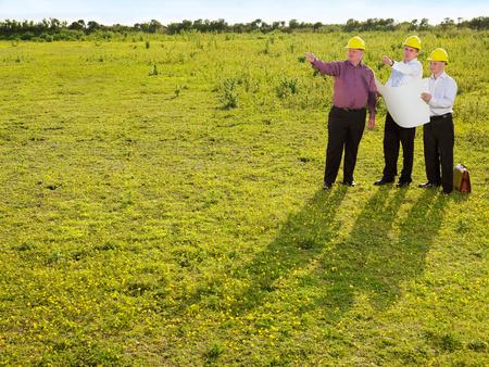 Three surveyors on a field. Stock fotó