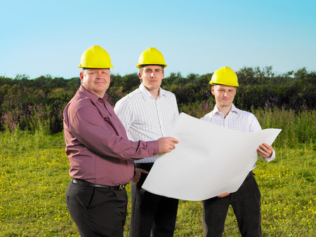 Three surveyors on a field.
