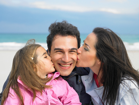Mother and daughter kissing father