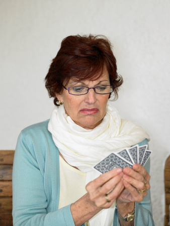 Senior woman playing cards pulling face Stock Photo