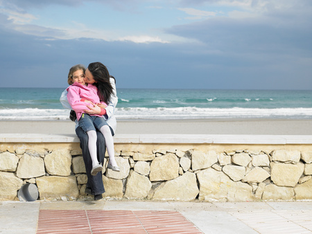 Mother and daughter sitting on wall